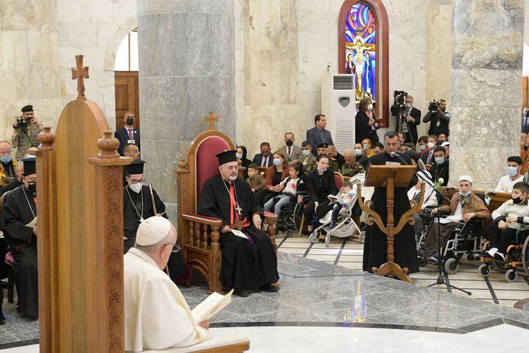 In de kerk van de Onbevlekte Ontvangenis in Qaraqosh luistert paus Franciscus naar de toespraak van priester Ammar (rechts achter het spreekgestoelte). Beeld EPA
