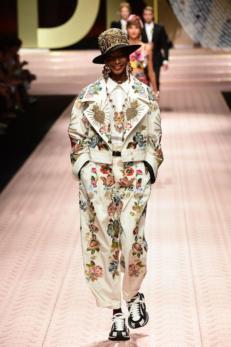 Een setje met een kort jasje en broek in dezelfde beige kleur met bloemenprint op.