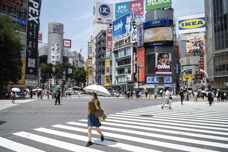 Een Japanse vrouw draagt een parasol tegen de zon in hartje Tokio. Beeld AFP