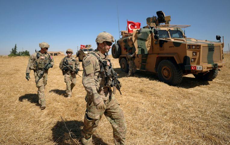 Amerikaanse soldaten patrouilleren samen met Turkse collega's bij de stad Tel Abyad in het noorden van Syrië. Beeld Reuters