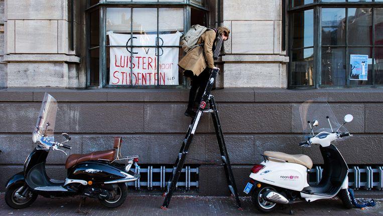 Een student klimt in het bezette Bungehuis, het gebouw van de faculteit geesteswetenschappen van de Universiteit van Amsterdam. Beeld ANP