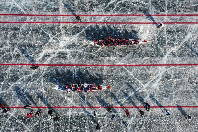 Hier kunnen we in Nederland slechts van dromen: een drakenbootrace op natuurijs.  In China, waar de drakenboot vandaan komt, is het winterse folklore. Zoals te zien  bij deze wedstrijd in Shenyang, in de noordoostelijke provincie Liaoning, waar het  al dagenlang vriest dat het kraakt.  Beeld AFP