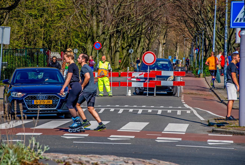 Het Kralingse Bos zondagmiddag. De toegangswegen waren afgesloten en verkeersregelaars stuurden automobilisten weg, maar wandelaars en fietsers konden er wel door door.