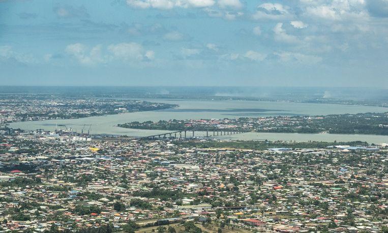 Luchtfoto van de Surinaamse hoofdstad Parmaribo met in het midden de Jules Wijdenboschbrug.  Beeld Rowin Ubink