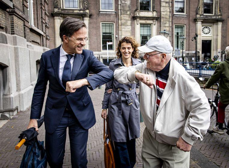 Mark Rutte (VVD) geeft een voorbijganger een elleboog na afloop van de hervatting van de formatiegesprekken bij het Logement.  Beeld ANP