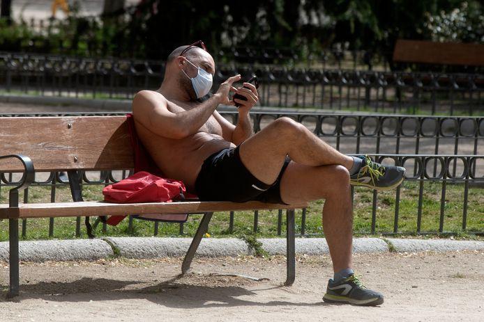 Un homme portant un masque facial pour se protéger contre la propagation du coronavirus utilise son téléphone portable dans un parc tout en profitant du temps ensoleillé à Madrid, en Espagne, dimanche 28 mars 2021.