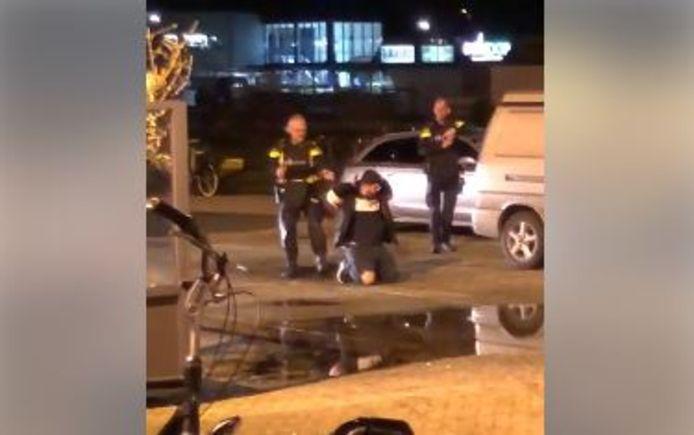 Een van de verdachten wordt onder schot gehouden tijdens de arrestatie.