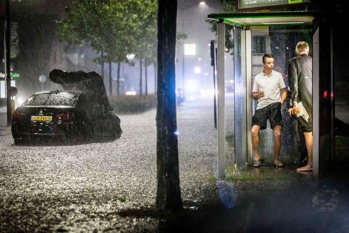 Twee mannen schuilen in een bushokje, terwijl op 23 juni enorm noodweer over Zuidoost Brabant trekt. Het noodweer richtte voor honderden miljoenen euro's schade aan.