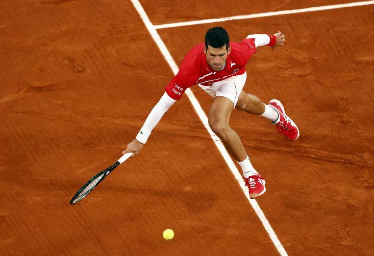 Novak Djokovic haalt een bal achter de baseline. Beeld EPA