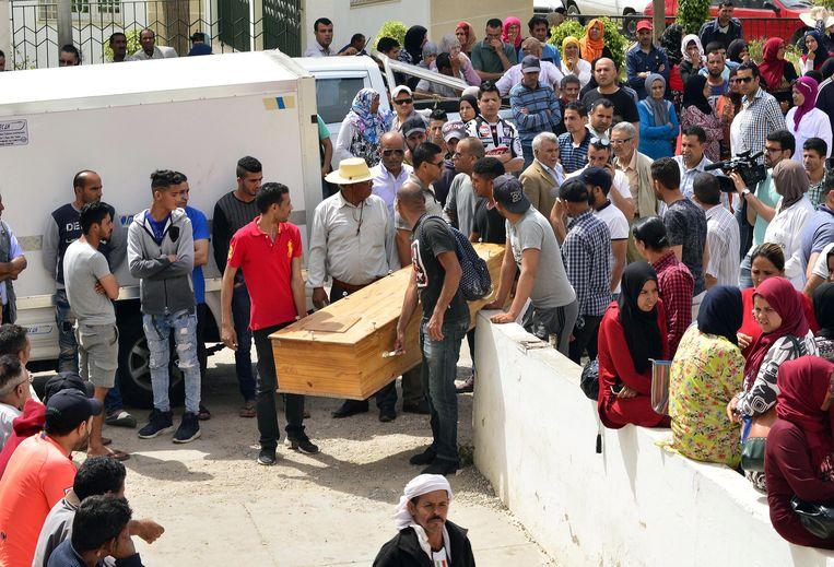 Enkele mannen dragen het lichaam weg van één van de mensen die omkwam bij de boottocht. Beeld EPA