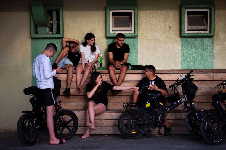Israëlische jongeren genieten zonder mondkapjes van de zon in Tel Aviv.  Beeld AP