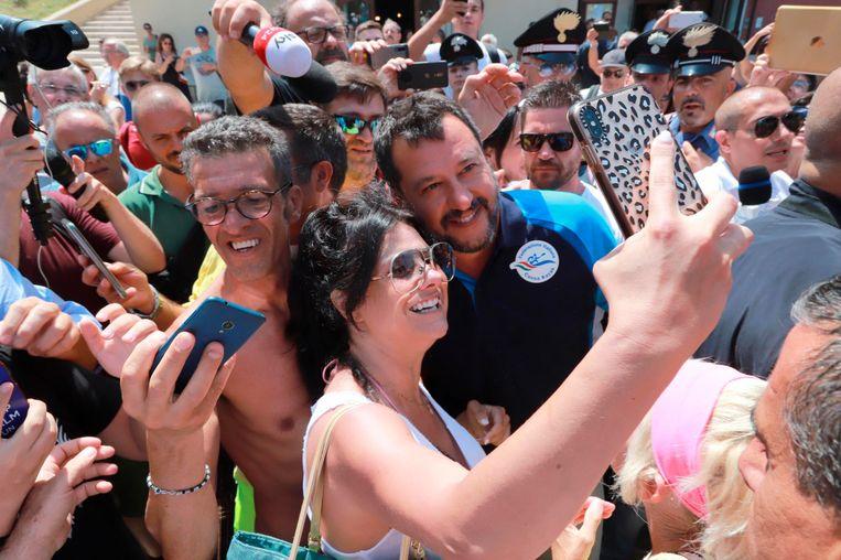 Matteo Salvini poseert voor selfies met zijn supporters aan hetLido Cala Sveva in Termoli. Dit vormt een onderdeel van zijn 'Italiaanse zomertournee'.  Beeld AP
