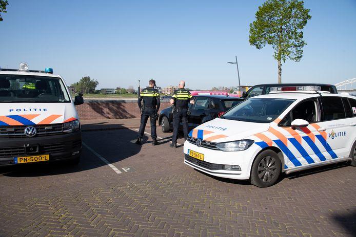 Politie-agenten bekeuren een automobilist aan de Waalkade. Hij bleek zonder rijbewijs te rijden.