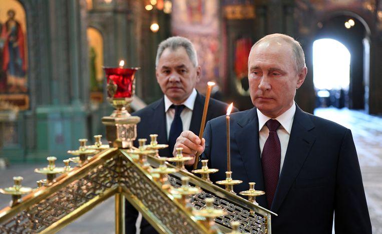 President Poetin en defensieminister Sergej Sjojgoe branden een kaars in de oorlogskerk.  Beeld EPA