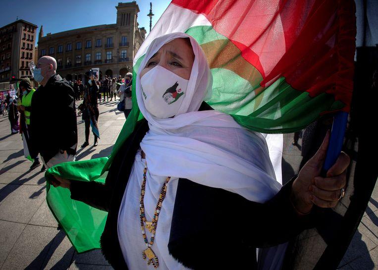 Een vrouw houdt een Sahara-vlag vast tijdens een bijeenkomst en hekelt de 'illegale bezetting' door Marokko in Pamplona, Noord-Spanje. De bijeenkomst markeert de 45e verjaardag van de uitroeping van de Democratische Arabische Sahara-Republiek. Beeld Hollandse Hoogte / EPA