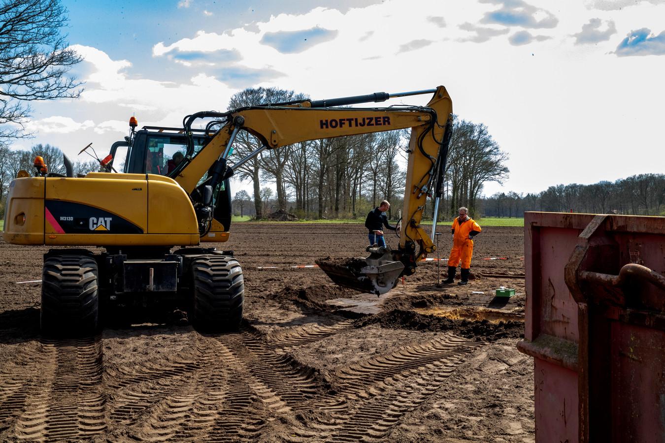 De vervuilde grond wordt gesaneerd terwijl een milieudeskundige (oranje overall) bodemmonsters neemt.