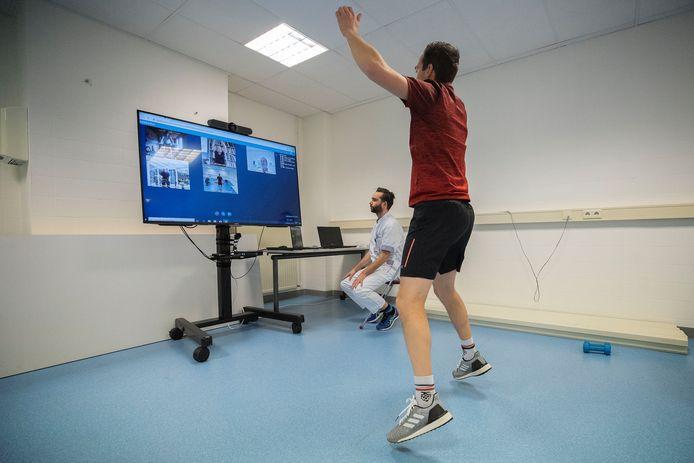Bewegingsagoog Rob Schepers doet een oefening voor, terwijl fysiotherapeut Coert van de Schoot het scherm in de gaten houdt.