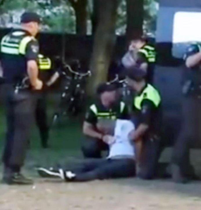 Agenten slepen het bewegingsloze lichaam van Mitch Henriquez naar de arrestatiewagen.