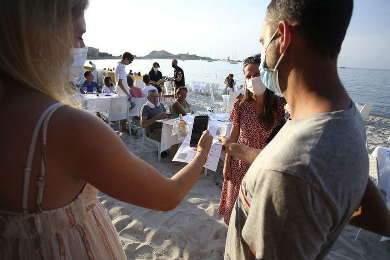 Een check van het covidpaspoort van een klant voor een restaurant op het Franse eiland Corsica.  Een digitaal paspoort is inmiddels verplicht in Frankrijk voor restaurants, sportclubs, bioscopen, musea en theaters, en tegelijk zijn PCR-testen in het land niet meer gratis. Zo wordt (gratis) vaccinatie aantrekkelijker en goedkoper. Beeld AFP