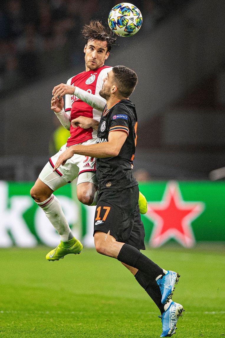 Nico Tagliafico (Ajax) wint kopduel van Mateo Kovavic (Chelsea) in de Champions League. Beeld