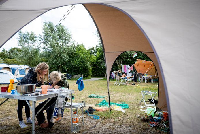 Jonge kampeerders bij hun tent op een natuurcamping van Staatsbosbeheer (Terschelling). Veel Nederlanders vieren vanwege het coronavirus dit jaar vakantie in eigen land.
