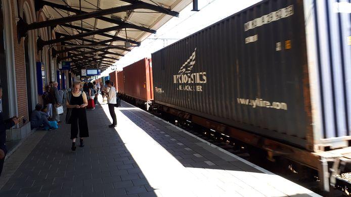 Goederentrein dendert voorbij station Dordrecht terwijl passagiers wachten.