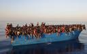 Een overvolle boot met honderden migranten voor de kust van het Italiaanse eiland Lampedusa. Beeld van 28 augustus.