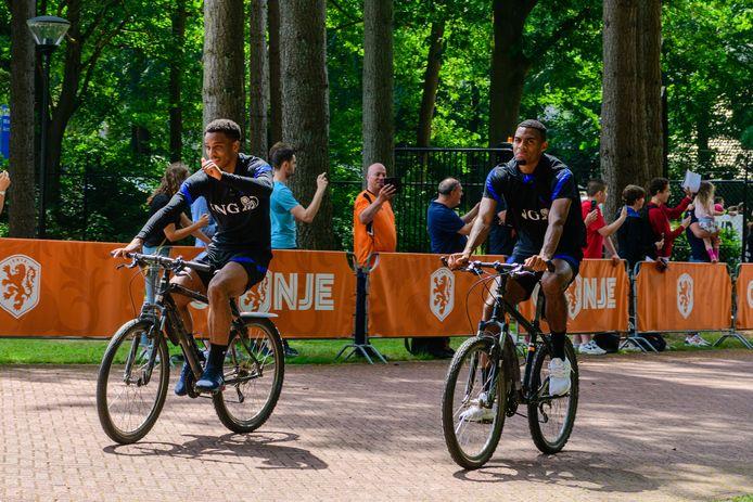 Utrechter Jurriën Timber steekt zijn duim op naar supporters langs de hekken. In het Oranje-shirt Marcel en naast Timber op de fiets Ryan Gravenberch.