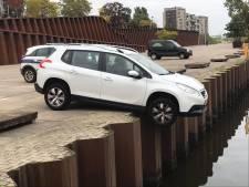 Oeps... de handrem vergeten; auto bungelt op Maaskade in Cuijk