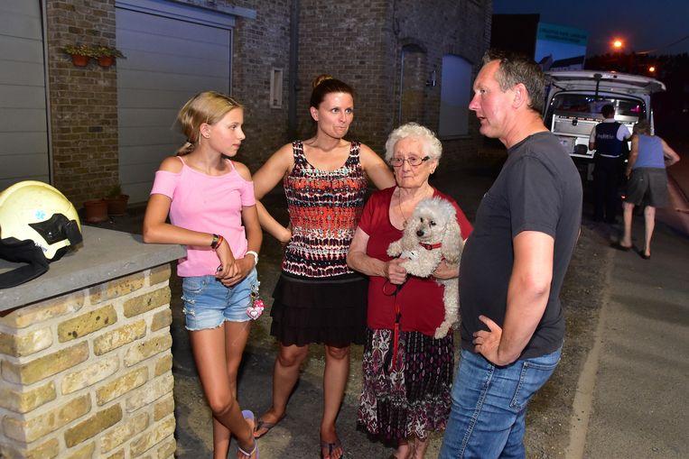 Jenny Debusschere (79) en haar hondje Prutske, omringd door enkele familieleden en burgemeester Kurt Windels, die polshoogte kwam nemen.