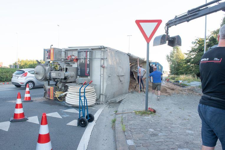 De vrachtwagen ligt naast de weg. Verkeer kan de snelweg nog op.