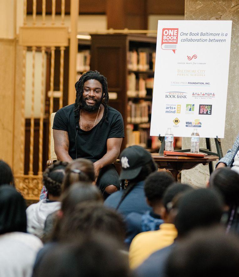 Jason Reynolds praat over zijn boeken met scholieren in Baltimore. 'Ik kan goed met jongeren praten, ik raak een snaar bij hen. Omdat ik ben en voel zoals zij zijn en voelen.' Beeld NYT/ANDREW MANGUM