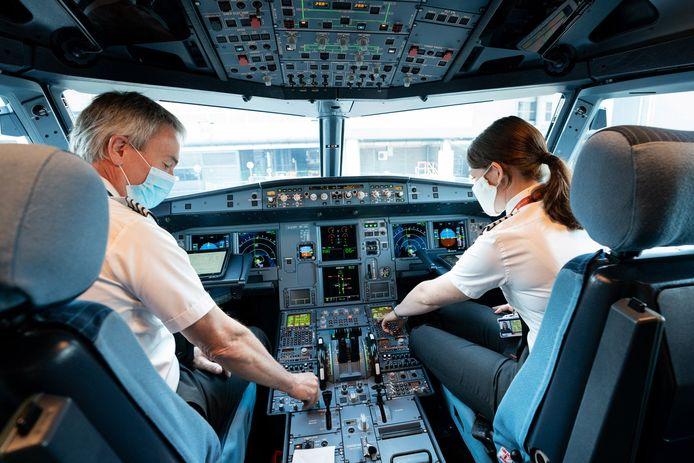 Piloten met mondkapjes op.