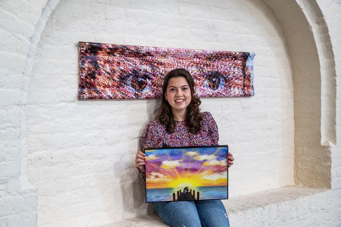 Roos Lammerse met de kunstwerken die ze voor het project heeft gemaakt: ,,De meeste klasgenoten maakten duistere werken, maar ik voel me daar niet prettig bij.'' Foto Ronald Hissink
