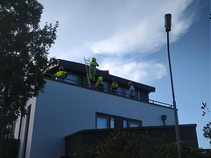 De brandweer verwijdert losse dakdelen van een woning aan de Kanteel in Dreumel.