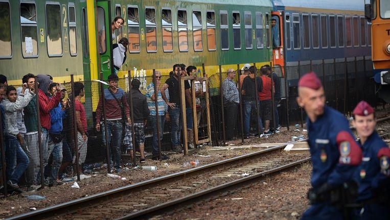 Gestrande vluchtelingen verschansen zich in in wagons op het station van Bicske. Beeld anp