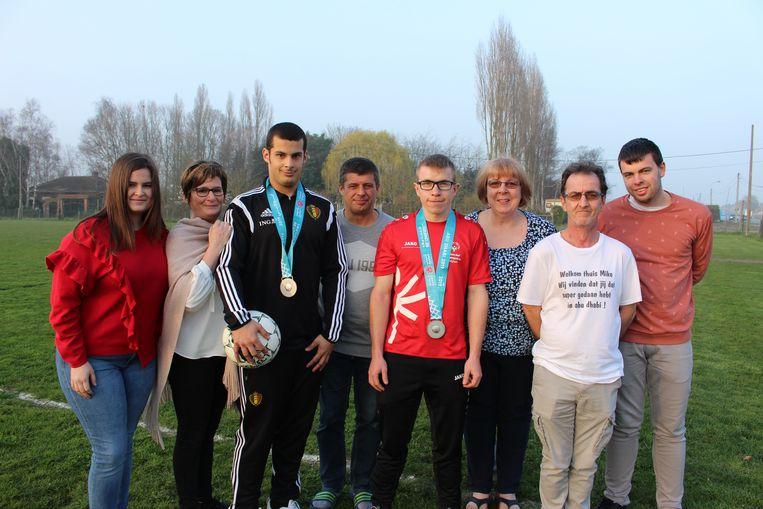 Bram Verbrugghe uit Ardooie en Mike Watteyn uit Rekkem, met de zilveren medaille die ze enkele dagen geleden hebben behaald op de Special Olympics in Abu Dhabi. Hier staat ze tussen hun ouders Trui, Carl en Amber (gezin Bram) en Els, Patrick en Glenn (gezin Mike).