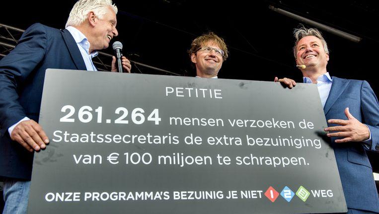 Staatssecretaris Sander Dekker (M) neemt op het Malieveld uit handen van omroepbestuurders Jan Slagter (L) en Henk Hagoort een petitie in ontvangst met meer dan 260.000 handtekeningen tegen de aangekondigde extra bezuinigingen van 100 miljoen euro bij de publieke omroep. Beeld anp