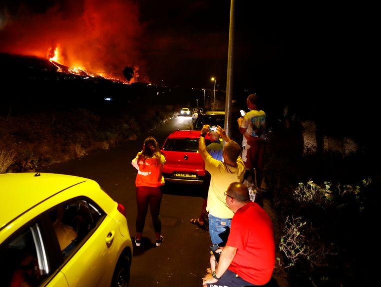 Bewoners kunnen het niet laten en nemen toch een kijkje bij de vulkaanuitbarsting. Beeld REUTERS
