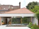Le nouveau volume – une construction basse avec une toiture en pavillon asymétrique adossée à une petite annexe existante – occupe toute la largeur de la parcelle.