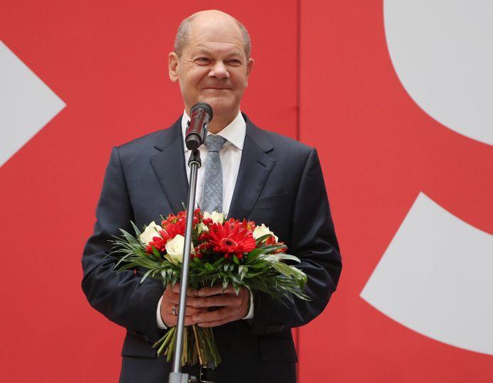 SPD-kanselierskandidaat Olaf Scholz maandagochtend met een boeket bloemen bij het hoofdkwartier van zijn partij in Berlijn als dank voor de verkiezingsoverwinning bij de Bondsdagverkiezingen van zondag.