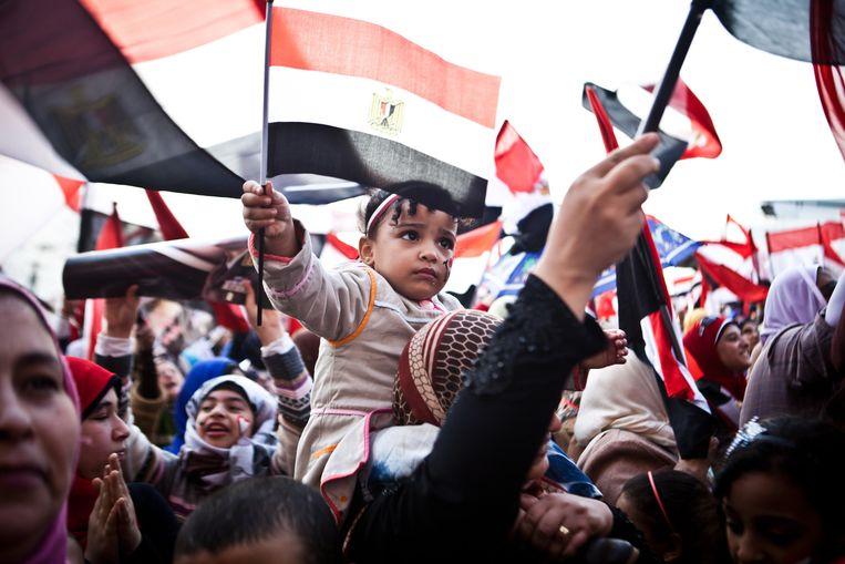 Egyptenaren zwaaien met de Egyptische vlag op het Tahrirplein in Caïro, tijdens een herdenking voor de verjaardag van de Arabische Lente. Beeld AFP