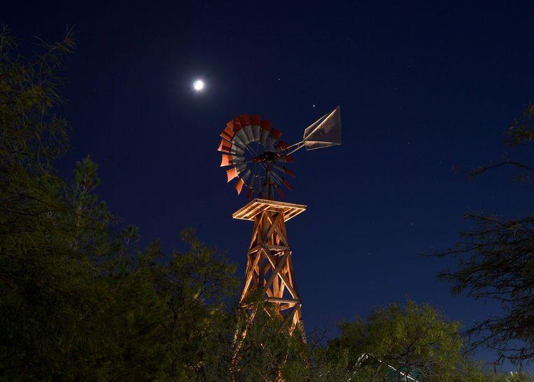 De maan en de planeten Saturnus en Jupiter zijn te zien boven een windmolen in Las Vegas. Beeld AFP