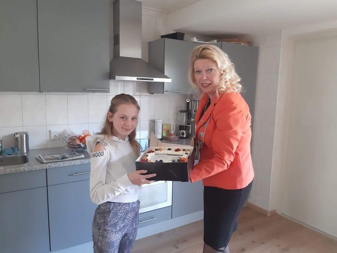 Jill ontvangt als 'Doener van de Maand' een taart, uit handen van burgemeester Willemijn van Hees.