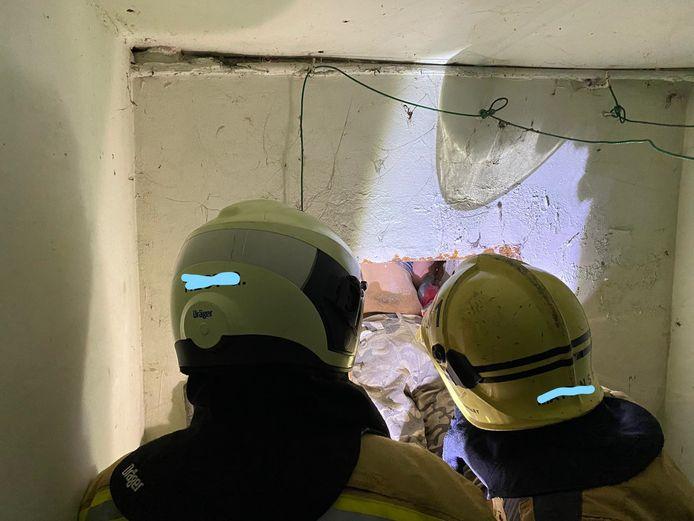 Brandweerlui onderzoeken in de woning hoe ze de man moeten losmaken.