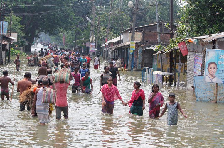 Inwoners waden door het water na een overstroming in West-Bengalen, India.