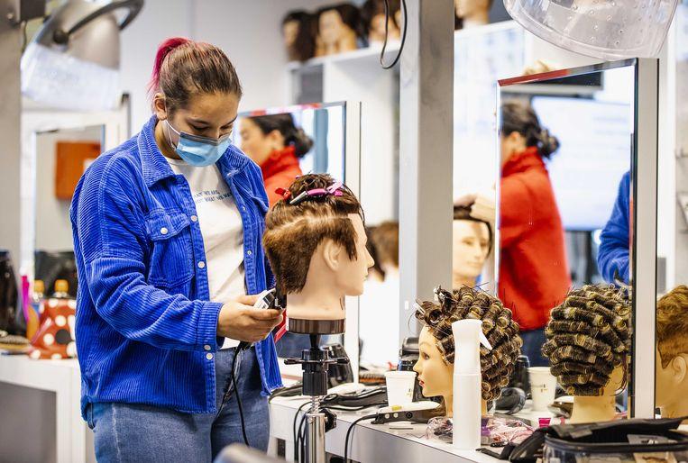 Een student van de opleiding beauty, hair & fashion aan het ROC Mondriaan in Den Haag. Juist in zwaar getroffen sectoren blijven jongeren langer doorstuderen nu het lastig is om een baan te vinden. Beeld ANP