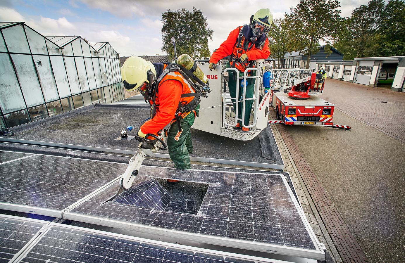 Op het dak van het fietsenhok oefent de Udense brandweer op het doorzagen van zonnepanelen. Met de 'Multicut' is er snel een gat gemaakt.