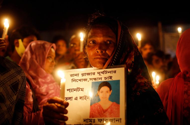 """A Bangladeshi woman holds a candle with a portrait of a missing relative, victim of last year's Rana Plaza building collapse, during a gathering to pay tributes on the eve of the tragedy in Savar, near Dhaka, Bangladesh, Wednesday, April 23, 2014. More than 1,100 people were killed when the illegally constructed, 8-storey building collapsed on April 24, 2013, in a heap along with thousands of workers in the five garment factories in the building. Placard reads """"Farzana, Rana Plaza missing."""" (AP Photo/A.M. Ahad) Beeld AP"""