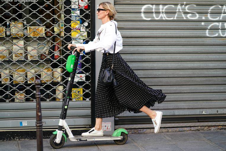 Bezoeker aan de Paris Fashion Week deze zomer verplaatst zich per trottinette, de overal aanwezige deelstep. Beeld Getty Images